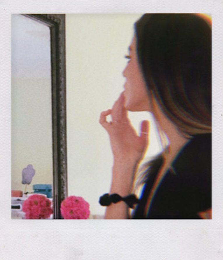 Maddie Applying Lip Gloss in The Mirror